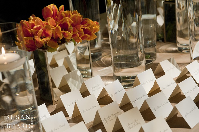 Elegant hand calligrahed escort cards line up on the place card table. Evantine Design.