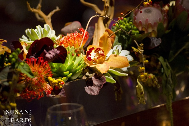 floral centerpieces with orange orchids green succulents yellow roses manzanita branches